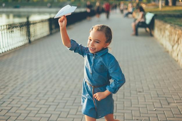 Dziewczyna bawi się, biegając z papierowym samolotem zabawki