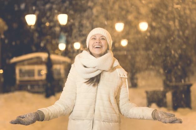 Dziewczyna bawi się na boże narodzenie dekoracji światła ulicy. młoda szczęśliwa uśmiechnięta kobieta nosi stylowy szalik z dzianiny i kurtkę na zewnątrz. model się śmieje. zima w krainie czarów, impreza sylwestrowa.