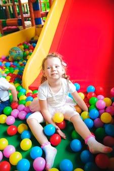 Dziewczyna bawi się na placu zabaw, w labiryncie dla dzieci.