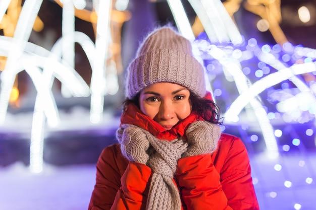 Dziewczyna bawi się na świątecznych dekoracjach świeci ulica młoda szczęśliwa uśmiechnięta kobieta ubrana stylowo