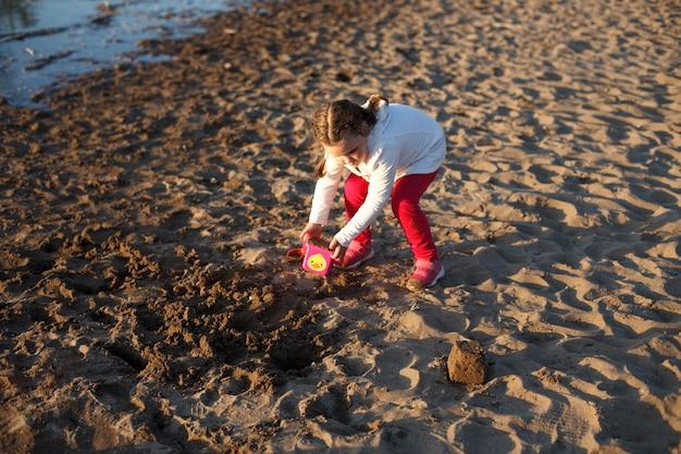 Dziewczyna bawi się piaskiem na piaszczystej plaży nad brzegiem rzeki podczas zachodu słońca.
