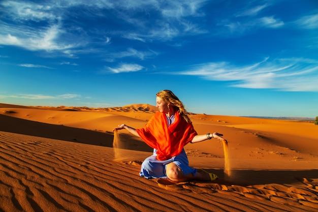 Dziewczyna bawi się piaskiem na saharze. erg chebbi, merzouga, maroko.