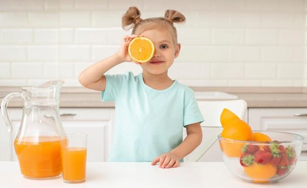 Dziewczyna bawi się pomarańczą w domu