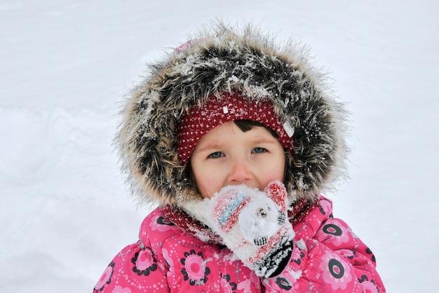 Dziewczyna bawi się śniegiem w zimie.