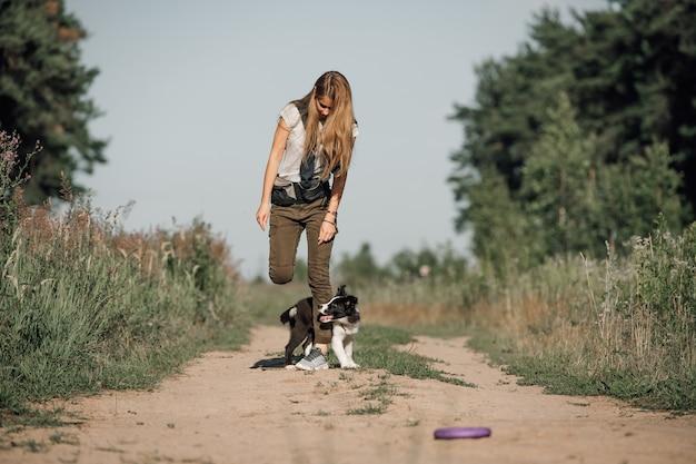 Dziewczyna bawi się z czarno-białym border collie szczeniak na leśnej ścieżce