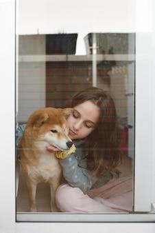 Dziewczyna bawi się ze swoim psem shiba inu, siedząc na podłodze w swoim pokoju obok okna.