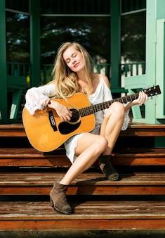 Dziewczyna bawić się gitarę outdoors lata pojęcie