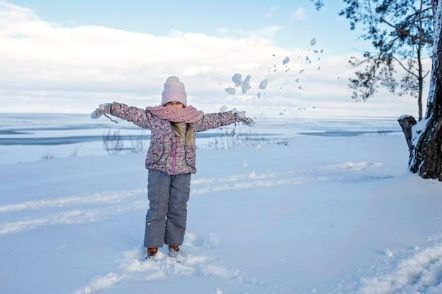 Dziewczyna bawić się na zamarzniętym jeziorze w śnieżny zimowy dzień, sezonowe zajęcia na świeżym powietrzu, styl życia