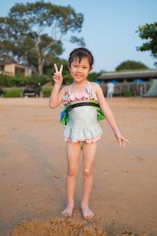 Dziewczyna bawić się piasek na plaży, dzieci bawić się w morzu