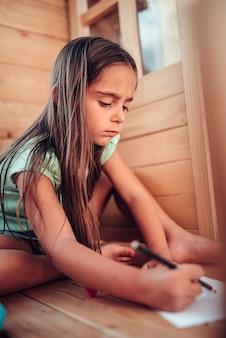 Dziewczyna bawić się w domek na drzewie i rysuje z barwionymi ołówkami