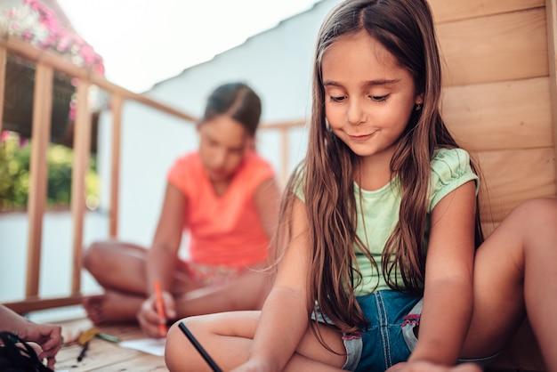 Dziewczyna bawić się w domek na drzewie z przyjaciółmi i rysuje z barwionymi ołówkami