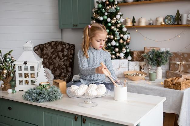 Dziewczyna bawić się w poranek bożonarodzeniowy kuchni w domu
