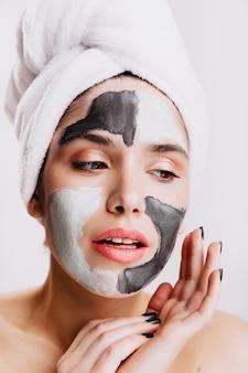 Dziewczyna bez makijażu robi swoje poranne rutyny na białej ścianie. pani używa glinkowej maski, aby poprawić wygląd skóry.