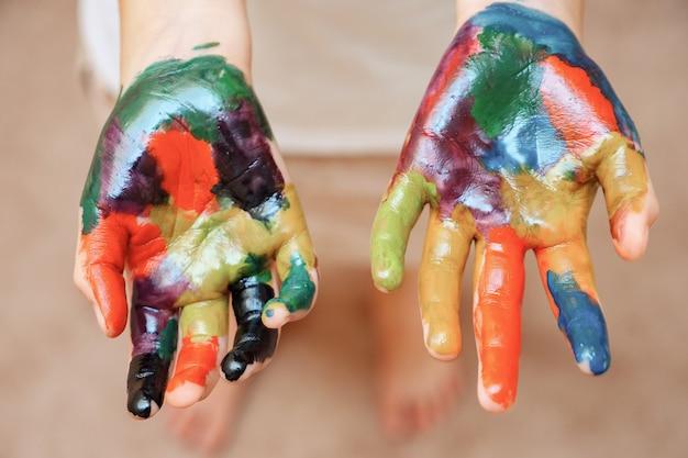 Dziewczyna bez twarzy, ręce w farbie, z bliska