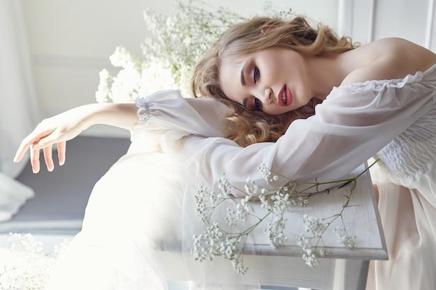 Dziewczyna białe światło sukienka i kręcone włosy kwiaty