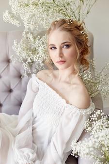 Dziewczyna białe światło sukienka i kręcone włosy, portret kobiety z kwiatami w domu