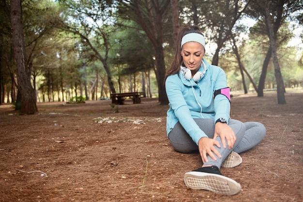 Dziewczyna biegacza z kontuzją kostki trzyma stopę, aby zmniejszyć ból po biegu. problem dla sportowców trenujących na świeżym powietrzu