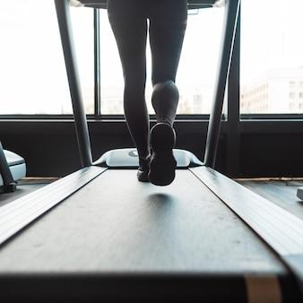 Dziewczyna biegająca na bieżni w siłowni, zbliżenie