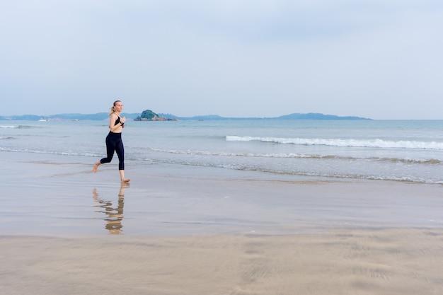 Dziewczyna biegnie wzdłuż plaży, uprawiając sport