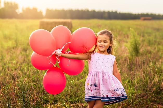 Dziewczyna biegnie z czerwonymi balonami w lecie w przyrodzie