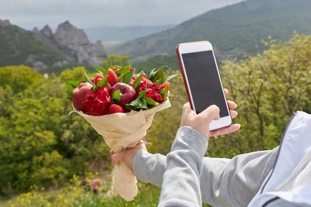 Dziewczyna bierze bukiet czerwonych kwiatów i owoców w aparacie telefonu