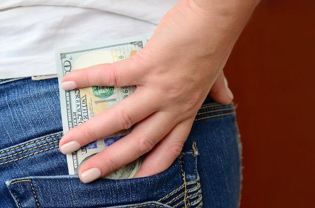 Dziewczyna bierze dużo banknotów dolarowych z tylnej kieszeni dżinsów