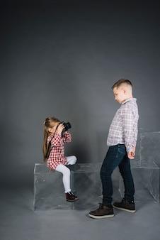 Dziewczyna bierze fotografię chłopiec z kamerą przeciw popielatemu tłu