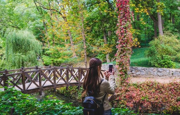 Dziewczyna bierze na telefon piękny krajobraz w parku