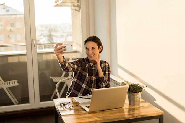 Dziewczyna bierze selfie z domowego biura podczas gdy ma przerwę od projekta