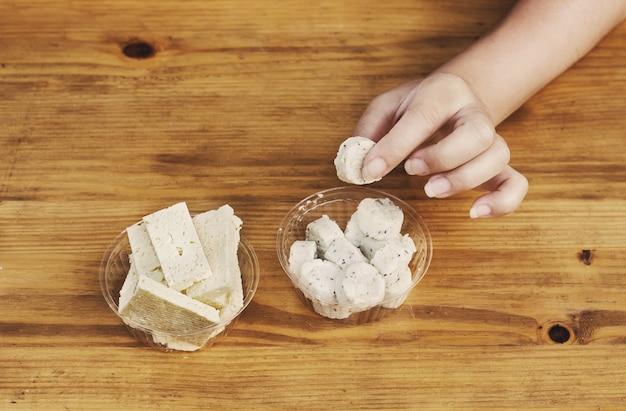 Dziewczyna bierze w rękę kawałek owczego sera z ziołami