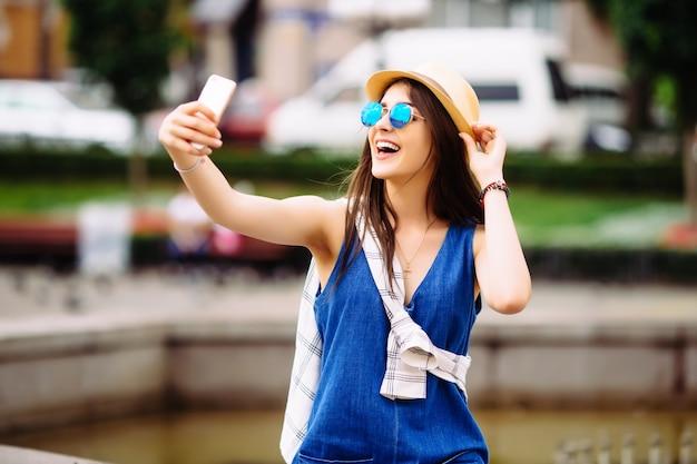 Dziewczyna biorąc zdjęcie selfie w pobliżu fontanny na zewnątrz
