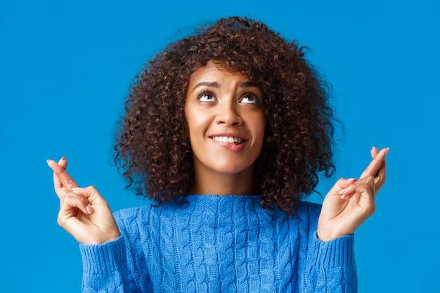Dziewczyna błagająca bóg, jej marzenie się spełniło. urocza i głupia afroamerykańska kręcona suczka z afro fryzurą, przygryzająca warga z pokusy i pożądania, kciuki powodzenia patrzą żebranie