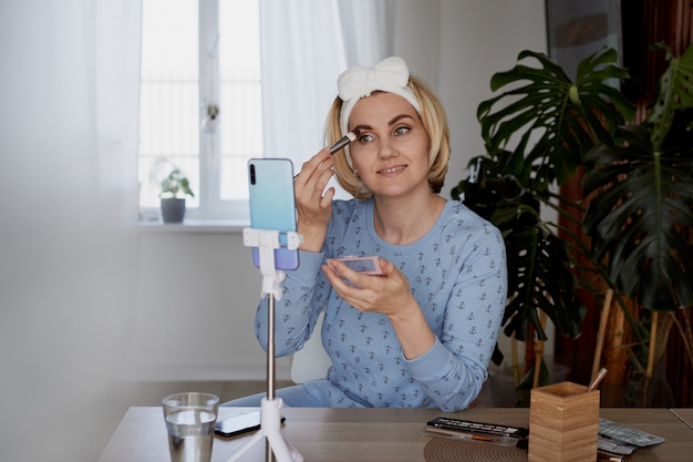 Dziewczyna-blogerka opowiada subskrybentom o pielęgnacji skóry i makijażu. koncepcja blogowania, transmisji i kosmetyków