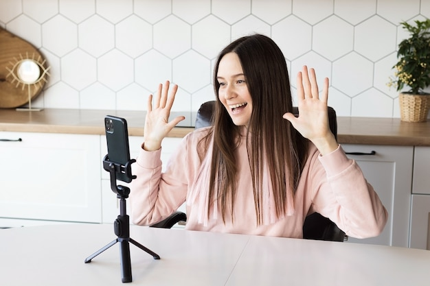 Dziewczyna-blogerka prowadzi transmisję na żywo ze swojego smartfona z domu