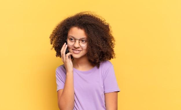 Dziewczyna całkiem afro nastolatek używając jej komórki