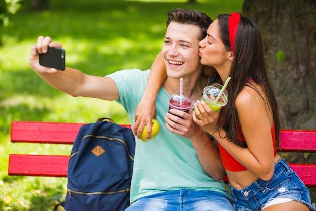 Dziewczyna całuje jej chłopak bierze selfie w parku