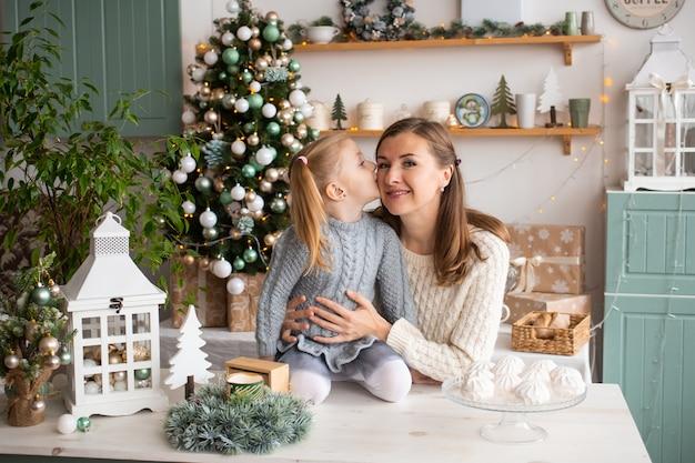 Dziewczyna całuje jej matki podczas gdy siedzący na kuchennym stole w bożych narodzeniach w domu.