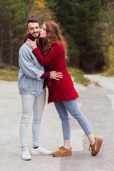 Dziewczyna całuje przystojnego chłopaka pełny strzał