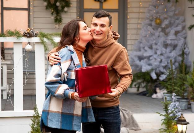 Dziewczyna całuje swojego chłopaka i gratuluje mu. trzymają czerwone pudełko z prezentem walentynkowym