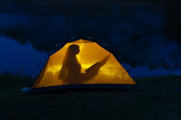 Dziewczyna camping na pustyni. sylwetka dziewczyny czyta książkę w namiocie.