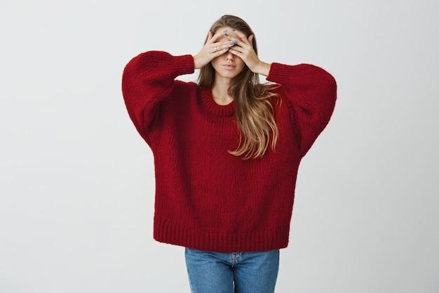 Dziewczyna chce uciec od świata i rzeczywistości. pracowniany portret stylowa szczupła kobieta w czerwonym luźnym swetrze zakrywającym oczy obiema rękami i stojący spokojny i zrelaksowany.