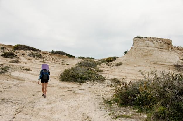 Dziewczyna, chodzenie po skałach z plecakiem