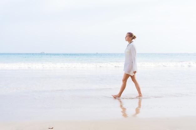 Dziewczyna chodzi po plaży iw wodzie