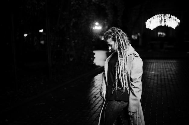 Dziewczyna chodzi przy nocy ulicą miasto z dreadlocks przeciw girland świateł.