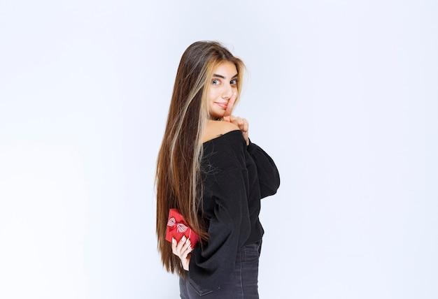Dziewczyna chowa za sobą małe czerwone pudełko upominkowe. zdjęcie wysokiej jakości