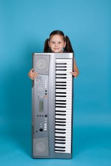 Dziewczyna chowająca się za pionowym elektronicznym syntezatorem i grająca na jego klawiszach