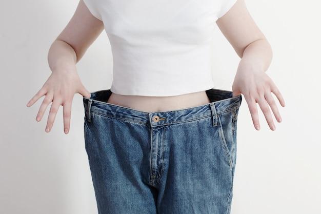 Dziewczyna ciągnie jej duże dżinsy i pokazuje utratę wagi
