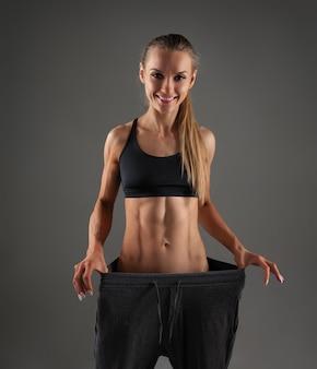 Dziewczyna ciągnie swoje duże spodnie i pokazuje utratę wagi
