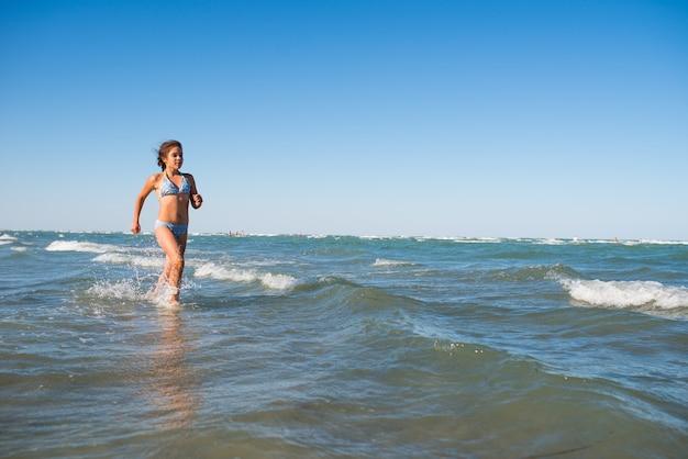 Dziewczyna, ciesząc się ciepłą bryzą, biegnie wzdłuż morza.