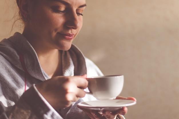 Dziewczyna cieszy się filiżanka kawy jedzenia blogger